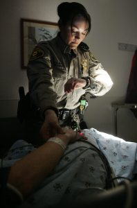 Deputy Kellie Hughes of the Linn County SheriffÕs Rescue program takes the pulse of a patient Suffering from a migraine in the St. Luke's ER Friday February 11, 2011. Deputies in the rescue program are trained paramedics who respond to calls in outlying areas. In between calls, they spend time in the ER helping with patients. (Becky Malewitz/SourceMedia Group News)