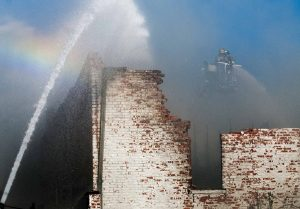 Fire crews douse the collapsed roof of a historic building in downtown Scott City after a fire broke out shortly after 1 p.m. The building located on the 400 block of Main Street was home to BraunÕs Butcher Block. Fire departments from several counties responded to the blaze and continued to work through the evening to put out hot spots.