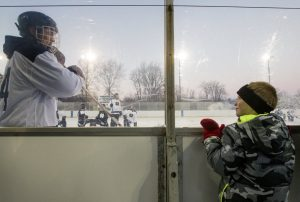 Notre Dame senior Thomas DiPauli interacts with Sam Hanson, 8, during Notre Dame Hockey's annual practice on the pond Monday, January 4, 2016 at Merrifield Park in Mishawaka.
