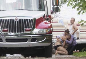 A woman breaks down and cries on the shore next to Baugo Bay as emergency crews respond after a toddler was reported to have fallen off of a boat Saturday June 13, 2015 in Osceola.