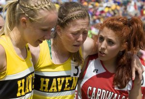 Haven senior Hailey Davis shows a mixture of disappointment and exhaustion as she is helped from the finish line by teammate Madison Caffrey and Sedgwick County's Melissa Olson after the girls 4 x 800 Class 3A State Championship, Saturday May 25, 2013, on the Wichita State University Campus. Haven placed second in the event.